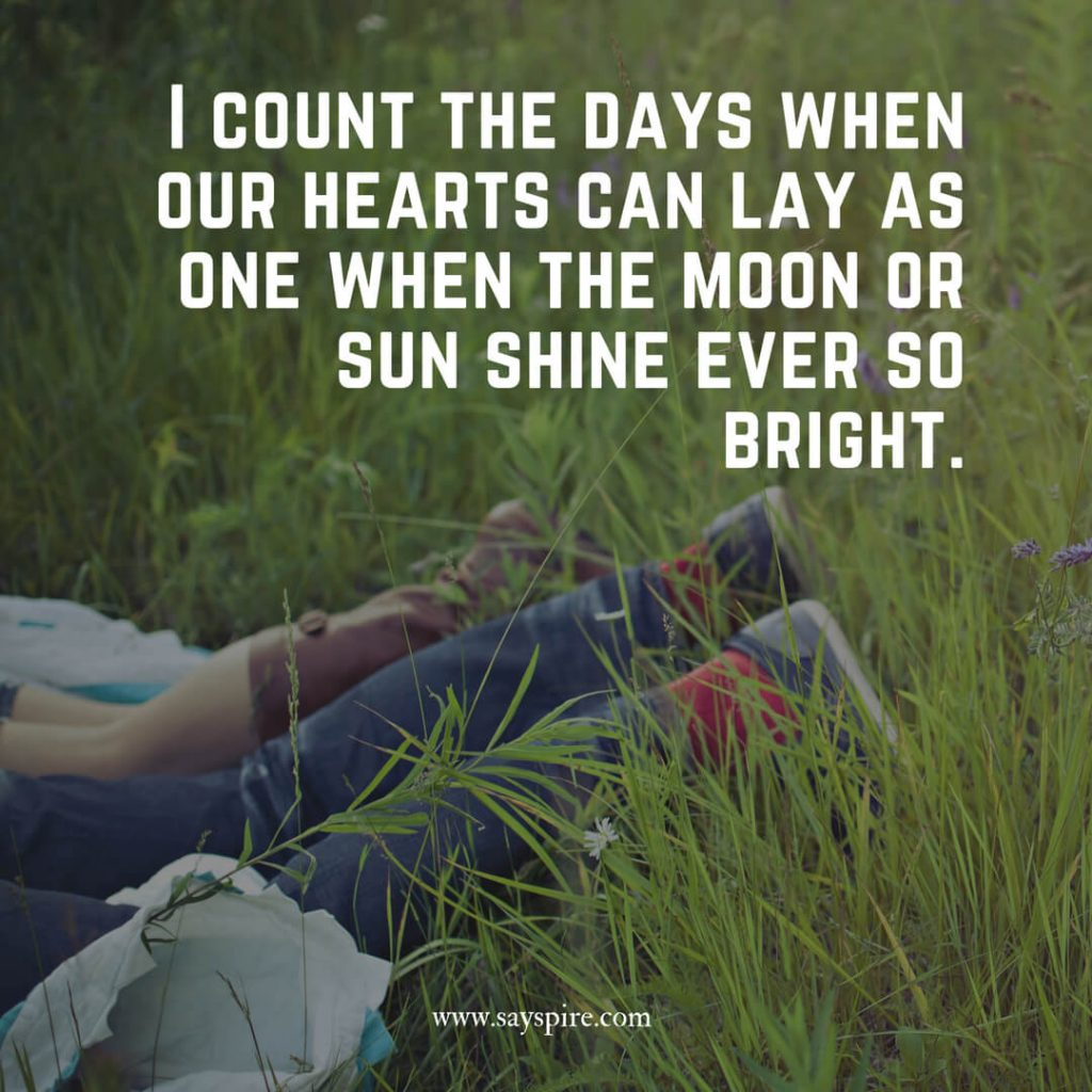 Two pairs of legs laying down in a grassy field with a thinking about you and missing you quote