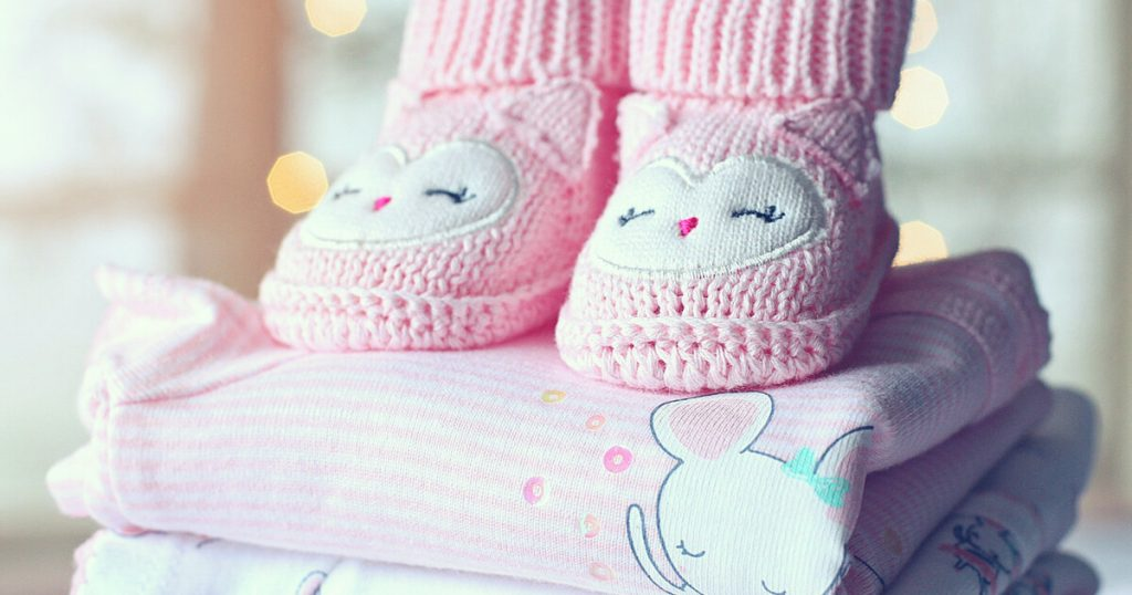 Pink booties atop baby clothes used in a growing up poem